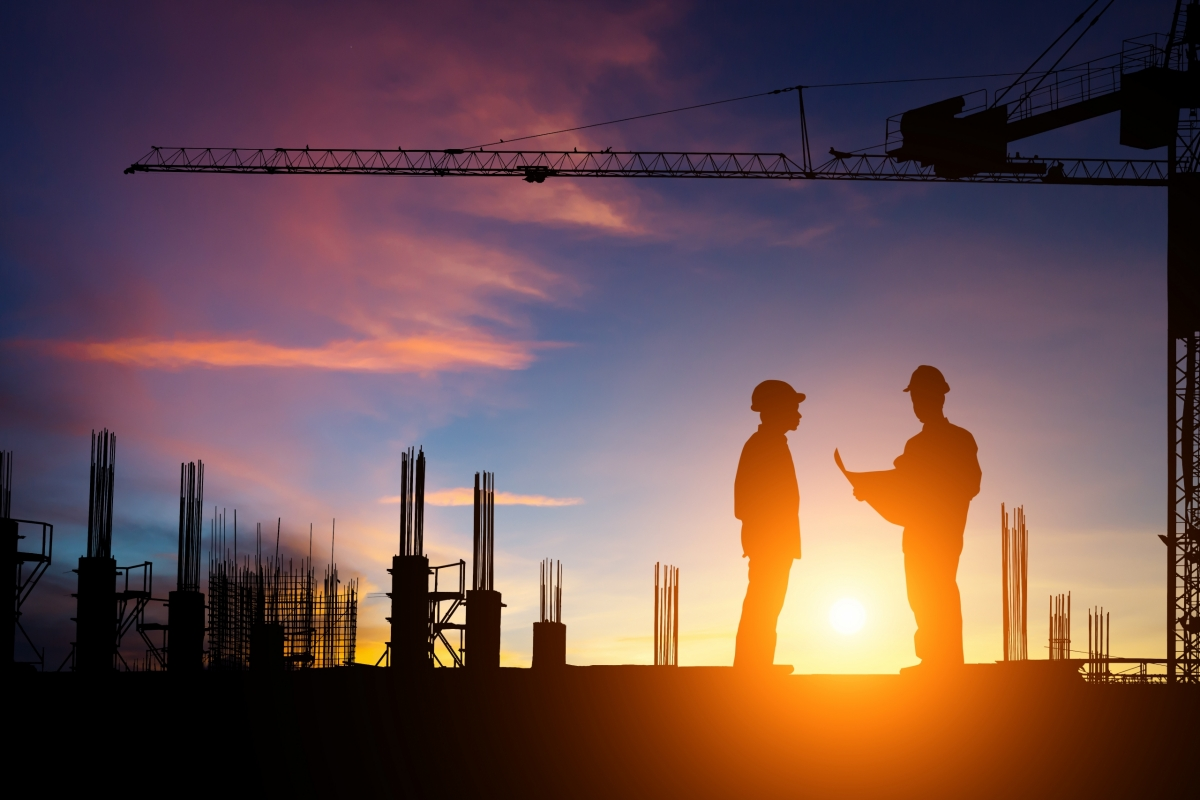 Two Builders Discussing a Drawing on a Site